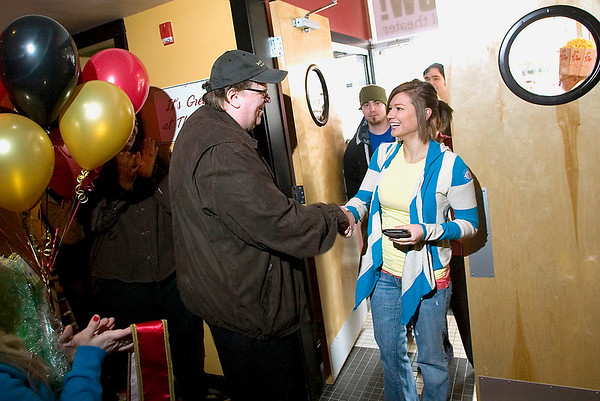 Record-Eagle file photo/Jan-Michael Stump<br /> Michael Moore greets Emily Martin, the 250,000th visitor to the State Theatre in Traverse City, which he helped restore. In this resort town of 15,000 on Lake Michigan, Moore's image is complex. Since moving to the area six years ago, Moore has become a high-profile citizen and benefactor.