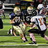 Record-Eagle/Keith King<br /> Traverse City St. Francis' Ashton Martenson is confronted by Elk Rapids' Emilio Bocardo, bottom right, Saturday at Thirlby Field.