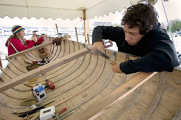 Record-Eagle/Keith King<br /> Eric Pentecost, right, and Lindsay Little, both of Traverse City, replace ribs as they work on restoring a Whitehall rowing skiff Saturday during the Michigan Schooner Festival. Petecost and Little are members of Sea Scouts and chartered through the Maritime Heritage Alliance.