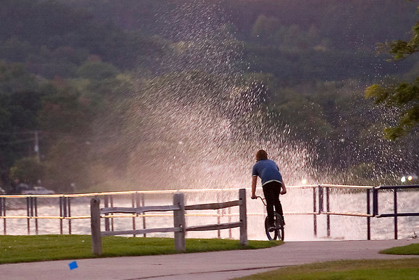 Record-Eagle/Jan-Michael Stump<br /> Devon Schubert, 17, rides his bike through the Open Space, where a north wind pushes waves over the breakwall Tuesday evening.