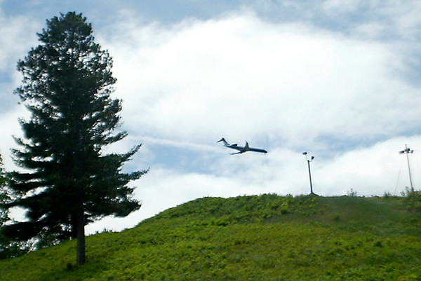 Record-Eagle file photo/Jan-Michael Stump<br /> A plane flies over Mt. Holiday in Traverse City. Air travel picked up at local airports despite a travel slump nationwide.