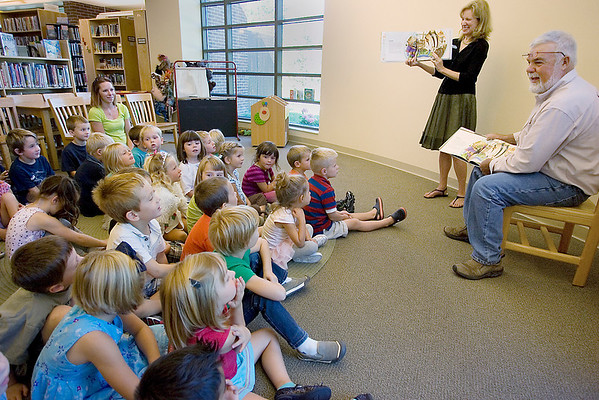 """Record-Eagle/Keith King<br /> Peninsula Township Supervisor Rob Manigold, right, next to Peninsula Community Library Director Vicki Shurly, reads """"Memoirs of a Goldfish,"""" by Michigan author Devin Scillian, to kindergarten and preschool students and teachers at the Old Mission Peninsula School."""