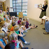 "Record-Eagle/Keith King<br /> Peninsula Township Supervisor Rob Manigold, right, next to Peninsula Community Library Director Vicki Shurly, reads ""Memoirs of a Goldfish,"" by Michigan author Devin Scillian, to kindergarten and preschool students and teachers at the Old Mission Peninsula School."