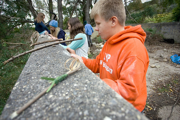 Record-Eagle/Keith King<br /> Zander Lensch, 13, reshapes a stone as he and classmates from the Greenspire School learn about early humans and the primitive tools they used for survival.