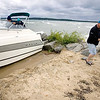 Record-Eagle/Keith King<br /> Sam Salisbury, of Traverse City, carries a downrigger from his friends' boat Friday as it sits along West End Beach after high winds washed it ashore.