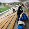 Record-Eagle/Keith King<br /> Kate Cizek, of Traverse City, lays down plastic sheets and towels Friday at Thirlby Field prior to the start of the varsity football game between Traverse City Central and Traverse City West. Cizek's son, Donny Cizek, plays on the Traverse City West football team.