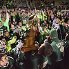Record-Eagle/Keith King<br /> Traverse City West players and fans cheer as Traverse City West varsity head coach Tim Wooer lifts the Nowak-Olson Trophy on Friday after defeating Traverse City Central 14-7 at Thirlby Field.