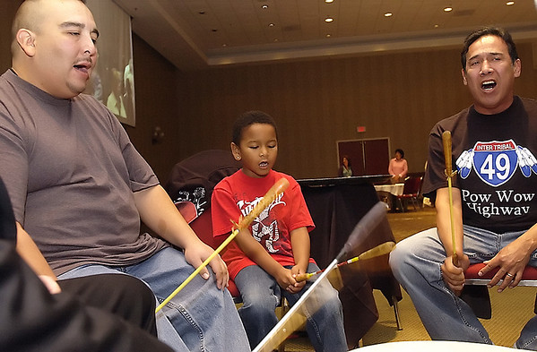 Record-Eagle/Garret Leiva<br /> Shocko Hall, left, Savante Hall, 6, center, and Karmen TwoCrow, right, perform with the Medicine Lodge Singers during opening ceremonies at the National Indian Council on Aging 2010 biennial conference.