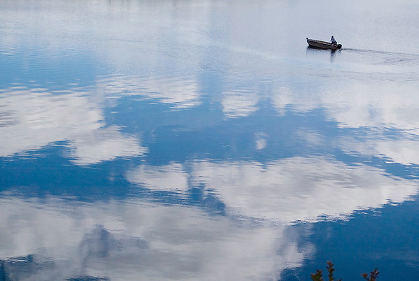 Record-Eagle/Jan-Michael Stump<br /> A fisherman cruises across a calm Boardman Lake under partly cloudy skies.