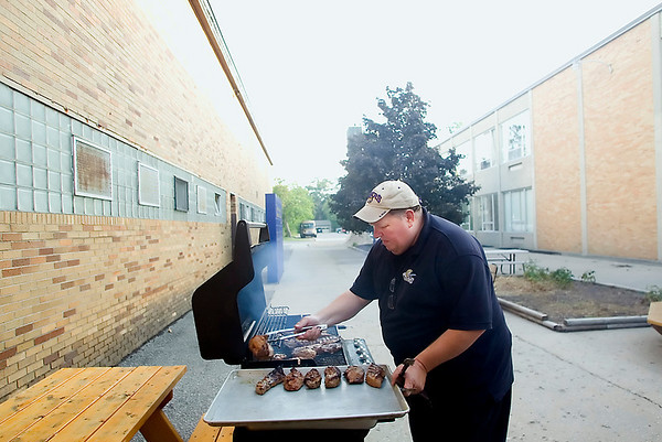 Record-Eagle/Jan-Michael Stump<br /> Doug Doty, father of St. Francis center Zac Doty, cooks steaks on a grill outside the school for the team's Monday-night dinner.