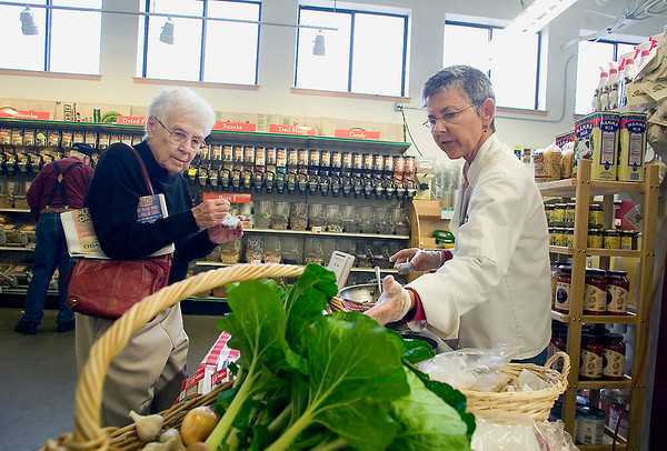 "Record-Eagle/Jan-Michael Stump<br /> Nancy Schwalm talks to Bert Rowley, left, of Virginia Beach, Va., about a bok choy and buckwheat noodles in seasoned broth recipe from the cookbook, ""What's For Dinner?"" on Monday at Oryana Natural Food Market."