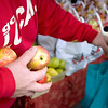Record-Eagle/Keith King<br /> Eric Mustard, of Maple City, holds SweeTango apples from Bakker's Acres to hand out as samples Saturday at the Sara Hardy Downtown Farmers Market.
