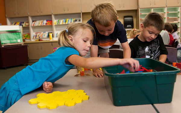 Record-Eagle/Douglas Tesner<br /> Kindergarten students Gabby Tucker, Reid Inglis and Cameron Brock use wooden blocks as they prepare to work on a math problem at Willow Hill Elementary on the first day of school.