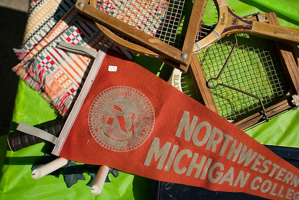 Record-Eagle/Jan-Michael Stump<br /> Old tennis rackets and a Northwestern Michigan College pennant sit for sale at Faye Brown's garage sale at her home on Fairlane Drive on Sunday. Labor Day weekend saw hundreds of garage sales in the Grand Traverse area.