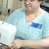 Record-Eagle/Lisa Perkins<br /> Tawni Gilmer, owner of Interquilten quilt shop in Interlochen, stitches quilts during the Helping Hands Quilting Marathon to benefit local uninsured breast cancer survivors.