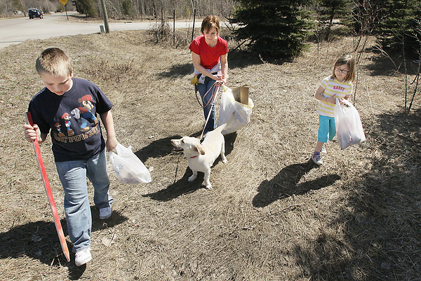 "Record-Eagle/Keith King<br /> Lana Watkoski, center, of Elmwood Township, walks with her son, Robert, 9; daughter, Lindsay, 5; and dog, Cierra, as they pick up trash along County Road 614 (Fouch Road) near Watkoski Road. ""I think we are all ready,"" Lana said about her appreciation of the mild temperatures. ""And it doesn't matter what we're doing, even if it's picking up trash."""