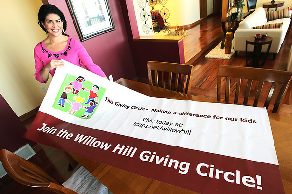 Record-Eagle/Keith King<br /> Jennifer Gaston, of Elmwood Township, holds a Giving Circle banner at her home.