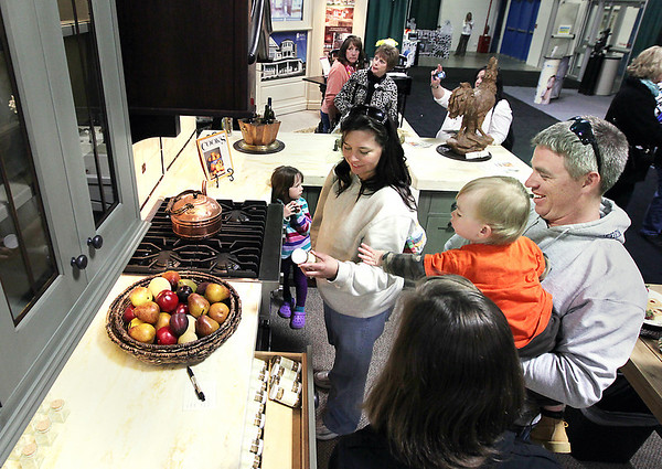Record-Eagle/Keith King<br /> J.C. Millikin, right, of Grayling, holds his son, J.C. Millikin, 1, as he and his wife, Toni Millikin, and daughter, Jocelyn Millikin, 5, look at the exhibit by Kitchen Choreography on Friday during the 'Up North' Lake and Cottage Show in Howe Arena at the Grand Traverse County Civic Center.