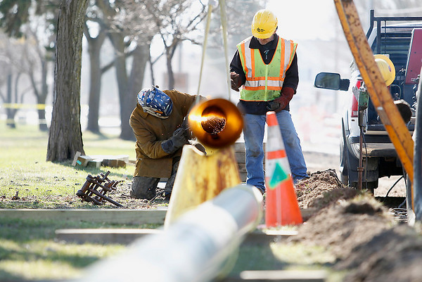 Record-Eagle/Jan-Michael Stump<br /> Dale Lantzer, of Miller Pipeline in Kalkaska, connects sections of gas pipe to be placed under the TART trail along Bay Street.