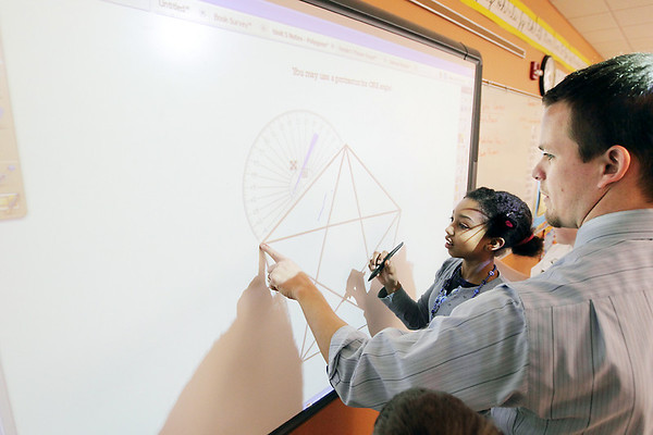 Record-Eagle/Keith King<br /> Tom Cooper, a teacher at Cherry Knoll Elementary School, assists Malytta Brown on an ActivBoard.