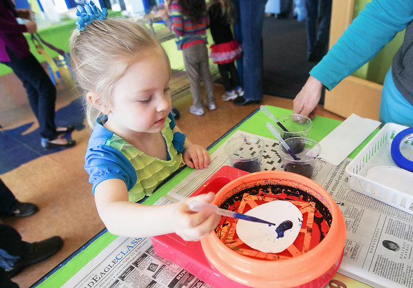 """Record-Eagle/Keith King<br /> McKinna Eckerle, 4, of Suttons Bay, applies drops of paint to an egg-shaped piece of paper prior to using an art spinner during the """"Egg-stravaganza"""" event at the Great Lakes Children's Museum in Elmwood Township."""
