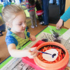 "Record-Eagle/Keith King<br /> McKinna Eckerle, 4, of Suttons Bay, applies drops of paint to an egg-shaped piece of paper prior to using an art spinner during the ""Egg-stravaganza"" event at the Great Lakes Children's Museum in Elmwood Township."