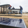 Record-Eagle/Keith King<br /> Chuck Bott, from left, Eric Heinz and Jerry Stricker, with Burkholder Construction, work at Oleson's Plaza East, in Traverse City, on a Bay Area Transportation Authority bus shelter which is to have solar-powered lighting.