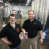 Record-Eagle/Keith King<br /> Russell Springsteen, left, Right Brain Brewery owner, and Scott Richards, Michigan Mobile Canning co-owner, stand Tuesday, April 16, 2013 in Right Brain Brewery holding Right Brain Brewery can design mockups.