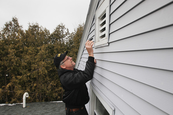 Record-Eagle/Keith King<br /> Joe Patterson, who with his wife, Sherri, owns Critter Control of Traverse City, performs an animal inspection Thursday, April 11, 2013 at a house in Leland.
