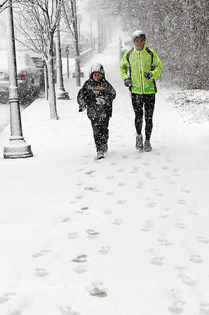 "Record-Eagle/Jan-Michael Stump<br /> Matt Johnston, right and his son Ryan, 10, run down Cass Street in the snow Tuesday afternoon. The two are part of the Run For God class at Central United Methodist Church, which is training for a 5K race in Cadillac on Memorial Day. ""When we left, there wasn't even any snow on the ground,"" said Emily Taphouse, another runner in the group."