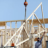 Record-Eagle/Jan-Michael Stump<br /> Workers from Northwest Carpentry place a roof truss on a unit in the Midtown development between Eighth Street and the Boardman River in Traverse City.