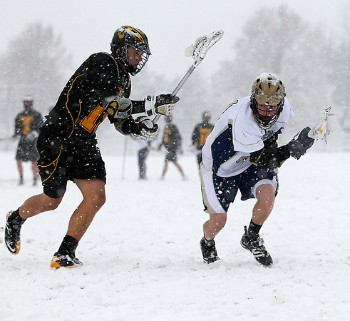 Record-Eagle/Jan-Michael Stump<br /> The TC Thunder Squirrels' Noah Parker (19) chases the TC Crusaders' Riley O'Neil (21) Tuesday on a snowy Carlisle Field.