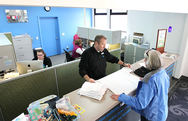 Record-Eagle/Keith King<br /> Scott Drzewiecki helps a customer as Megan Ruediger, back left, and Melanie Rojewski, back right, work nearby at JenTees Custom Logo Gear.