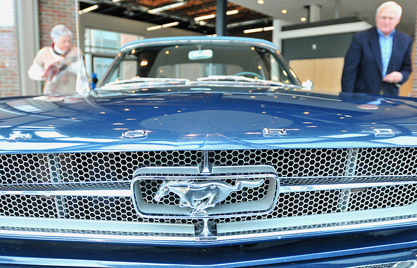 Record-Eagle/Nathan Payne<br /> Betty and Ed Mucha walk around their 1964 1/2 Ford Mustang inside the Hagerty Insurance headquarters on Cass Street in Traverse City. Mucha's Mustang was one of the first convertables to roll off of the assembly line 50 years ago.