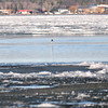 Record-Eagle/Nathan Payne<br /> A fisherman wades along the chanel at the mouth of the Boardman River where it enters West Bay. Ice still cloggs the beachfront along the south end of the bay more than a month after the first day of spring. Forecasters for the National Weather Service predict overnight low temperatures at or below the freezing mark for at least the next week.