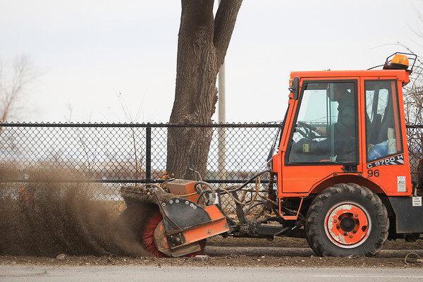 Record-Eagle/Keith King<br /> Dan Kowieski, with the City of Traverse City Streets Department, drives along Grandview Parkway as he operates a tractor with a brush attachment as workers with the department clean debris and sand from city roads after it accumulated over the winter.