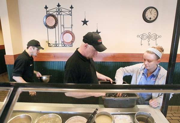 Record-Eagle/Keith King<br /> Dale McMahan, middle, an employee at Ponderosa Steakhouse in Traverse City, along with Mandi Lester, right, manager, and Michael Magee, left, prepare Wednesday, April 17, 2013 to open the restaurant for the day. McMahan's co-workers along with David and Donna Maxwell, owners of the restaurant, have pitched in to help in a variety of ways including raising money for McMahan after he and his family suffered a house fire on March 22.