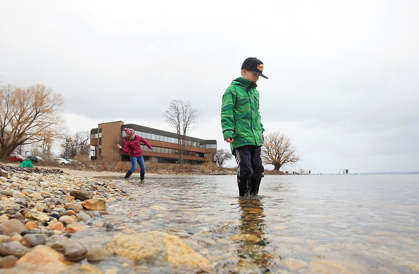 Record-Eagle/Keith King<br /> Lauren Ferris, back left, 12, of Traverse City, skips a stone while her brother, Ayden Ferris, 9, searches for other stones for skipping, or that look interesting, Friday, April 19, 2013 on West Grand Traverse Bay.