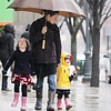 "Record-Eagle/Keith King<br /> Zane Schwaiger, middle, walks alongside her daughters — Amabel, sticking her tongue out, 5, and Ellen, 2 — as they travel through downtown on their way home. ""Gotta get out and get a little bit of fresh air,"" Schwaiger said of the rainy outdoor excursion."