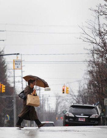 Record-Eagle/Keith King<br /> Carol Kingsley, of Mancleona, crosses Cass Street in the rain Tuesday, April 30, 2013 in downtown Traverse City.
