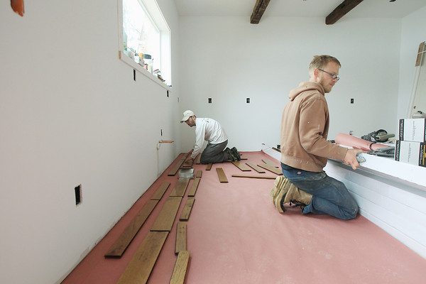 Record-Eagle/Keith King<br /> Jason Boudreault, left, and Clay Bowers, working with Grand Bay Building and Remodeling, install hardwood flooring Thursday, April 18, 2013 at a job site in Blair Township.