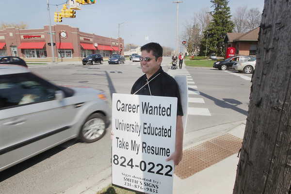 "Record-Eagle/Keith King<br /> Scott Chittle, of Manton, stands at the corner of Front Street and Division Street Tuesday, April 30, 2013 with a sign displaying his desire for a career. ""I did it a couple years ago and the response was fantastic, so I thought I'd give it a shot,"" Chittle, who has a bachelor's degree from the University of Michigan, said."
