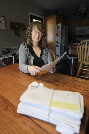 Record-Eagle/Keith King<br /> Ruth Schaub, of Suttons Bay Township, sits at her home Wednesday, April 17, 2013 near medical bills belonging to her father who has a variety of health issues.