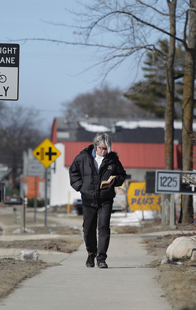 """Record-Eagle/Keith King<br /> Russell Byers, of Traverse City, walks along Woodmere Avenue as he reads a book he checked out from the Traverse Area District Library. """"I just like reading,"""" Russell said."""