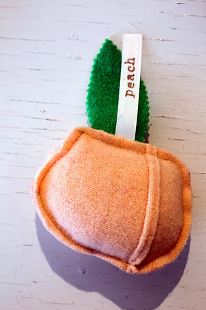 Record-Eagle/Jan-Michael Stump<br /> A peach, one of the vegetables Marcy Grudzien sews from old wool sweaters and sells at mecca, her Benzonia store, to raise money for the Grow Benzie Sewing Studio.