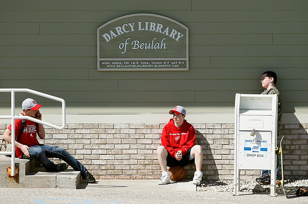 Record-Eagle/Jan-Michael Stump<br /> From left, Brett Harris, 15, Jesse Desroche, 15, and Keegan Milnickel, 10, wait for the Darcy Library of Beulah to open so they can use the Internet.
