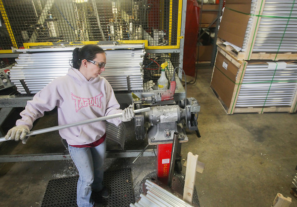 Record-Eagle/Keith King<br /> Lacey Buck uses a machine to rough the ends of a piece of aluminum, which will ultimately become a handrail, at Stromberg Carlson Products Inc. in Traverse City.