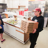 """Record-Eagle/Keith King<br /> Liz Carey, local Little Caesars employee, carries boxes of pizza which are to be served to people in need at the Traverse City Corps of the Salvation Army. The Little Caesars Love Kitchen, a mobile pizza kitchen, was parked in the parking lot of the Traverse City Corps of the Salvation Army to be utilized by local Little Caesars employees to make the pizza prior to the pizza being served by volunteers. """"I couldn't emphasize more the appreciation we have for the volunteers here,"""" John McFadden, director of social services at the Traverse City Corps of the Salvation Army, said. """"None of this would be possible without them or Little Caesars,"""" he said."""