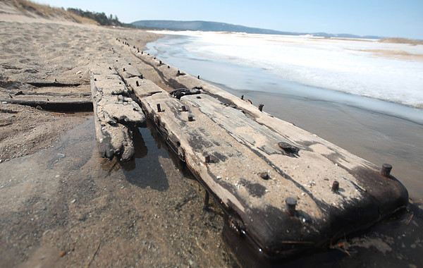 Record-Eagle/Nathan Payne<br /> The tip of a 40-foot-long section of a shipwreck juts out into the icy water of Lake Michigan near the Crystal River. Violent winter storms unearthed a large piece of what one archaeologist believes may be a 200 year old sailing vessel.