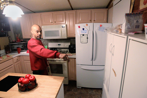 Record-Eagle/Keith King<br /> Lance Reed, of Grawn, points to evidence Monday, April 8, 2013 of where a bullet hit a cabinet door in his kitchen after the bullet was fired toward his home. Prior to hitting the door the bullet exited his old refrigerator.